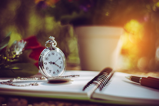 Image of desktop with pen, pocket watch and rose on an a spiral-bound notebook open to a blank sheet