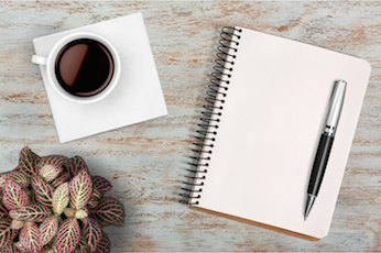 Image of a pen and notebook with a cup of coffee