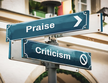 Image of street signs for Praise and Criticism pointing in different directions