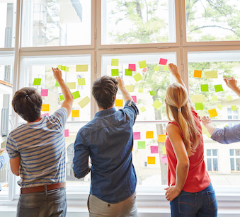 Image of people placing post-it notes on a window together