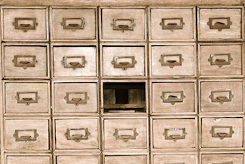 Image of a library card catalog missing a drawer