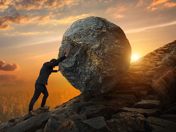 Image of a man pushing a boulder up a hill