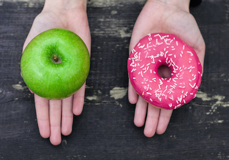 Image of two hands offering a donut or an apple