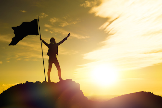 silhouettes of girl with flag of victory on the top of a mountain