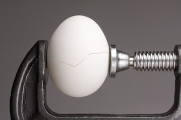 Image of egg cracking in a vise