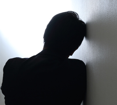 Image of worried man leaning against wall