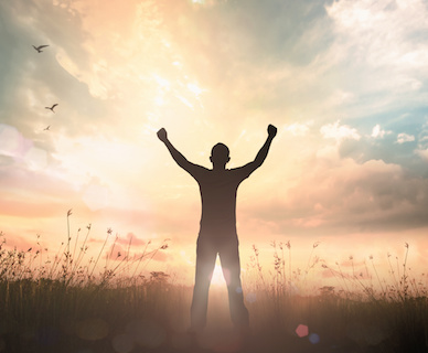 Image of a man with upraised arms facing sunrise
