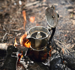 Image of coffee bubbling in a vintage kettle over a fire