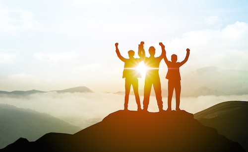 Image of team joining hands in triumph on a mountain peak