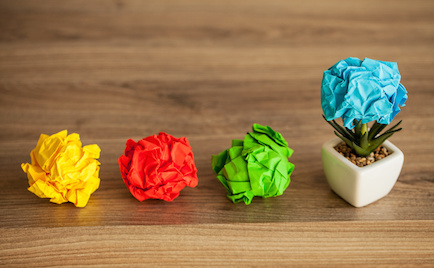 Image of crumpled ideas notes leading to success