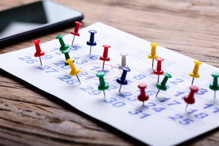 Calendar overcrowded with push pins for too many commitments