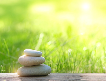 Image of three stones stacked in a beautiful garden