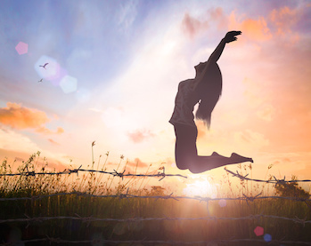 Image of woman leaping over barbed wire fence