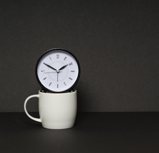 Image of a clock floating over a coffee cup