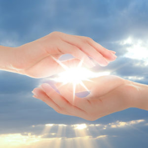 Image of Female hands holding sunlight on sky background