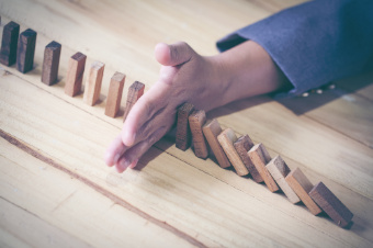 Image of Hand Stopping Dominoes