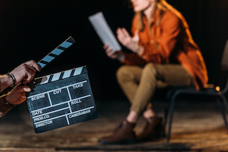 image of an actor reading from a script with a clapboard in front