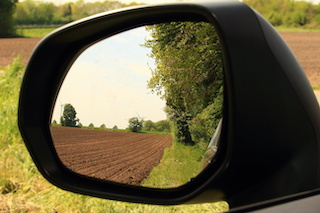 Image of rear-view mirror looking at a plowed field