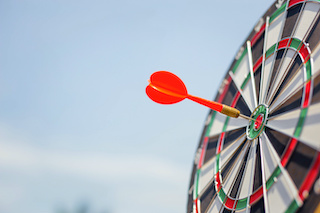 Image of a dart board with red-tipped dart in the bullseye with sky background
