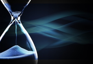 Image of an hourglass nearly out of time against dark blue background