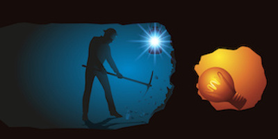 Man in underground tunnel digging with pickaxe towards a lightbulb in a small cave