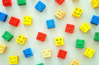 image of different emotions drawn on colorful cubes, wooden background.