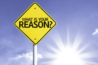"""Image of diamond-shape road sign that says """"What is your Reason?"""" with sky & sun background"""