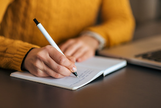Image of person in orange sweater writing in a notebook with a pen
